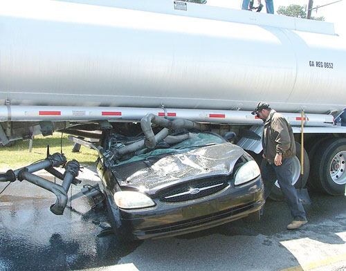 Car wedged under tanker